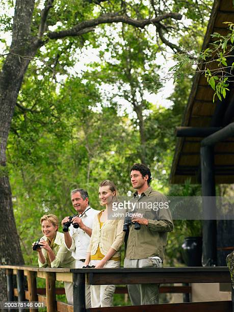 Two couples at lodge, three holding binoculars, smiling