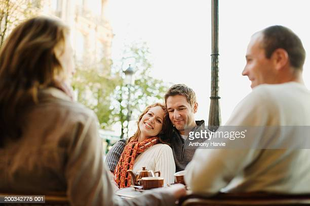 Two couples at outdoor cafe (focus on couple embracing in background)