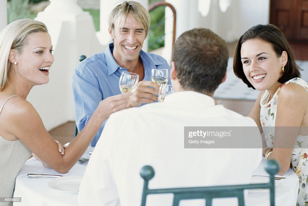 two couples at outdoor talbe making toast stock photo getty images