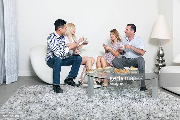 Two couples at teaparty in livingroom