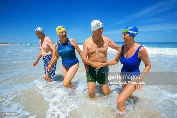 two couples coming out of ocean after swimming - sea swimming stock photos and pictures