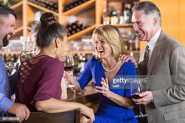 Two couples drinking, talking, laughing in bar