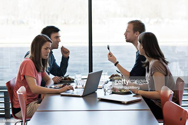 Two couples eating computers on table.