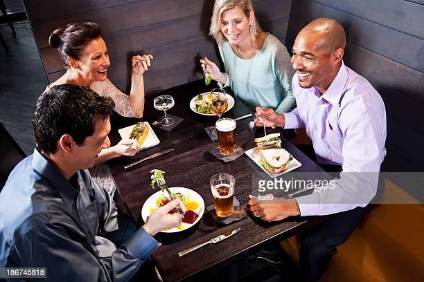 Dos parejas comiendo en un restaurante.