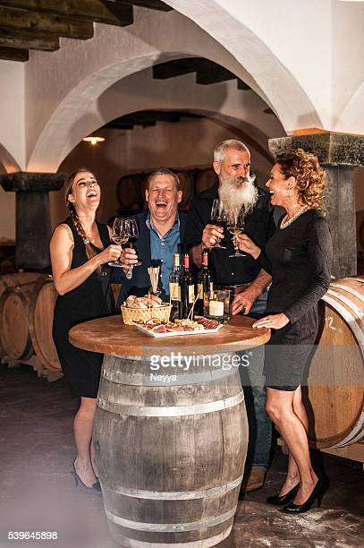 Two Couples Enjoying Food and Red Wine in Winery Cellar