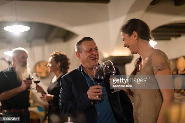 Deux Couples profitant de la cave à vin rouge, en Europe