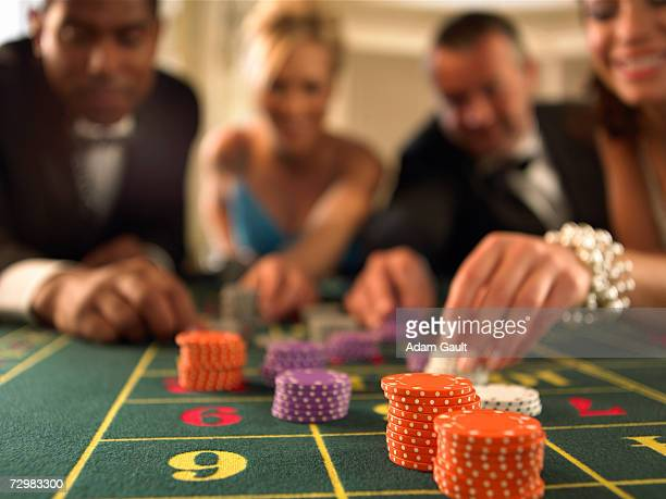 Two couples gambling in casino, focus on gambling chips