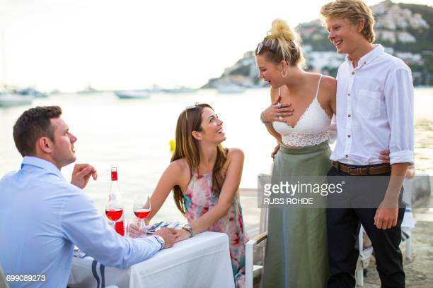 Two couples greeting at waterfront restaurant, Majorca, Spain