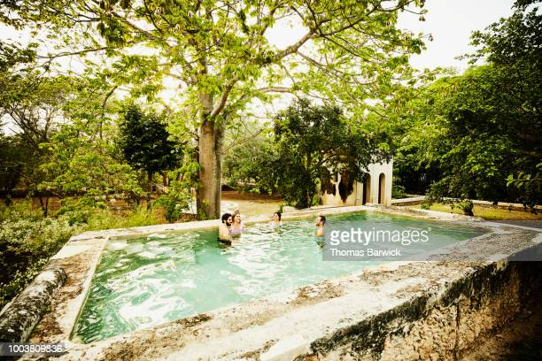 Two couples hanging out together in plunge pool at luxury tropical resort