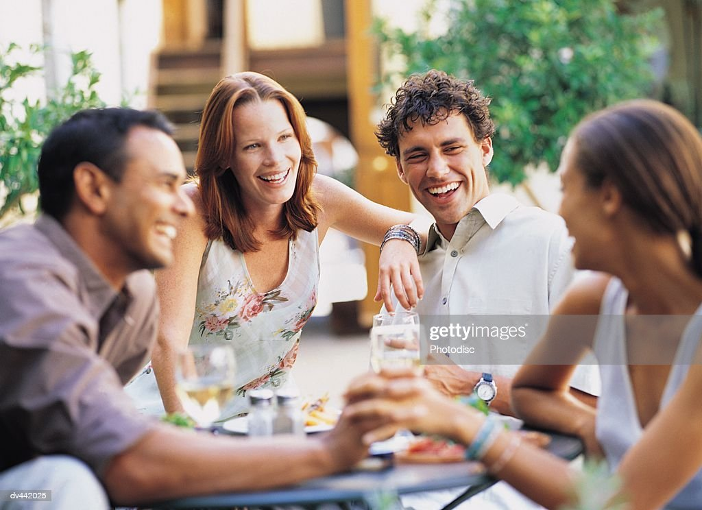 Two couples having a drink & chatting : Stock Photo