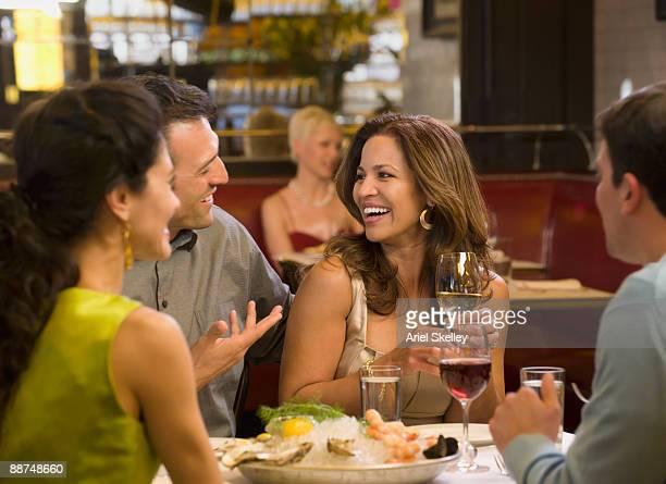 Two couples having dinner in restaurant