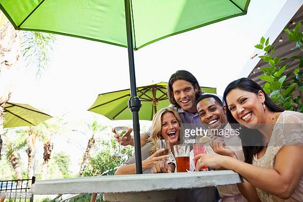 Two couples having drinks at outdoor cafe