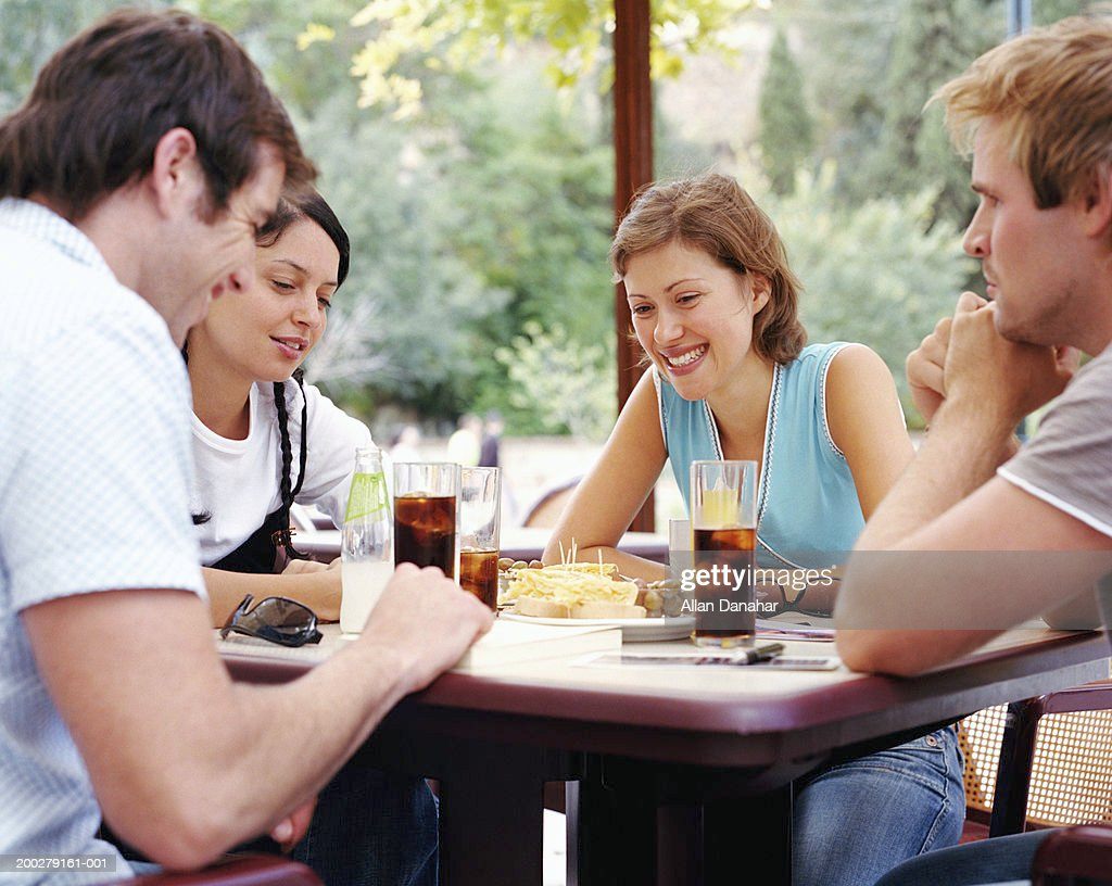 Two couples having drinks at outdoor cafe, smiling : Stock Photo