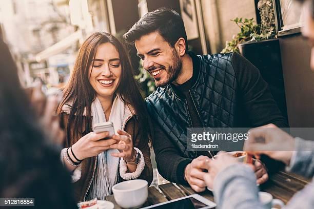 Deux couples s'amuser dans le café en plein air
