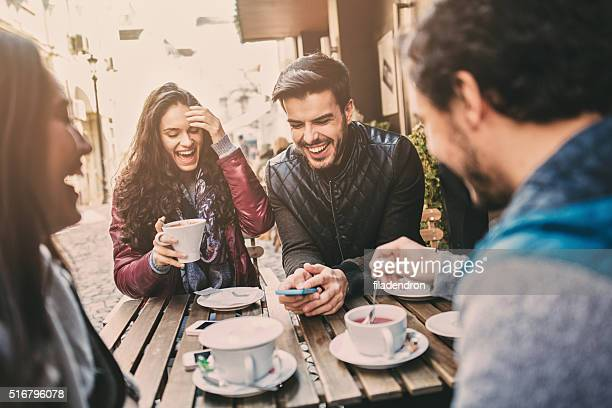 Two couples having fun in cafe outdoors