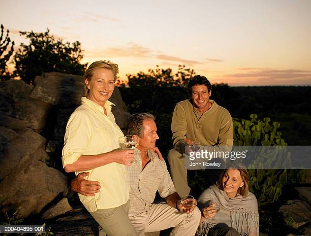 Two couples holding wine glasses outdoors, smiling, sunset