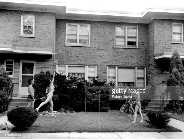 Two couples in bathing suits play badminton on the lawn in front of an apartment building on 6453 6451 N Whipple Street Chicago Illinois 1970s