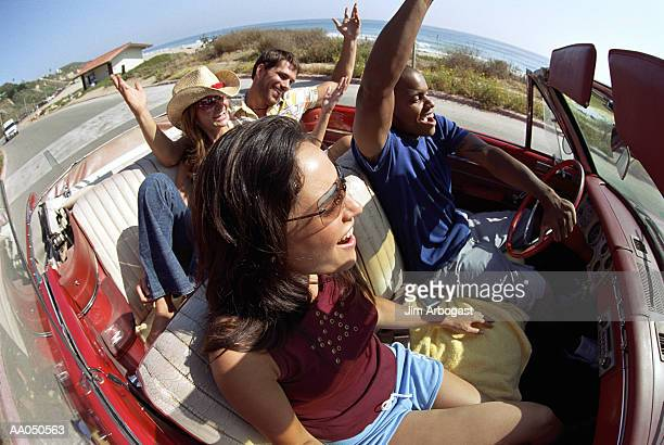 Two couples in convertible car (wide angle)
