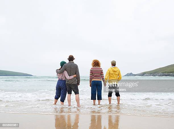 Two couples look out to sea from beach.