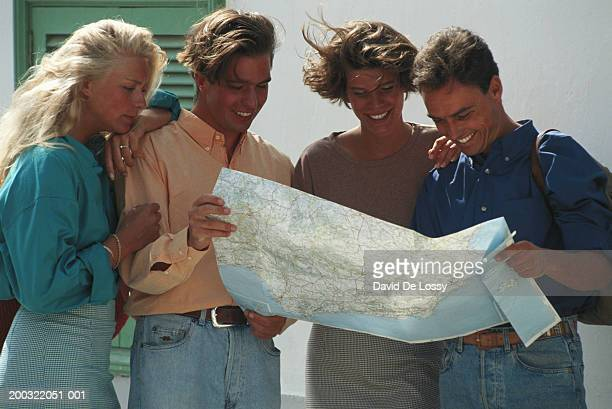 Two couples looking at road map outdoors, smiling