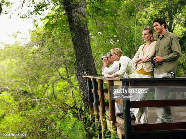 Two couples on balcony of lodge, man holding binoculars, smiling