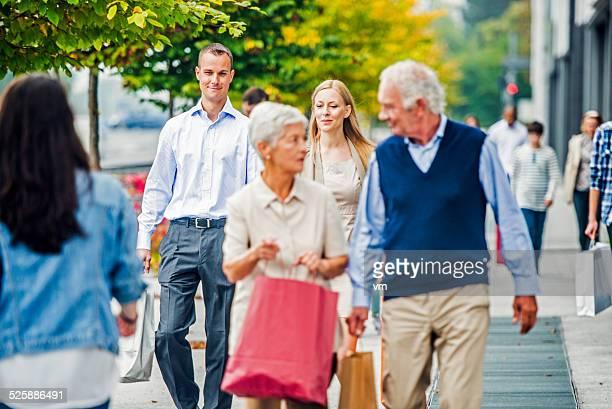 Zwei Paare auf überfüllten Stadt Straße nach Shopping