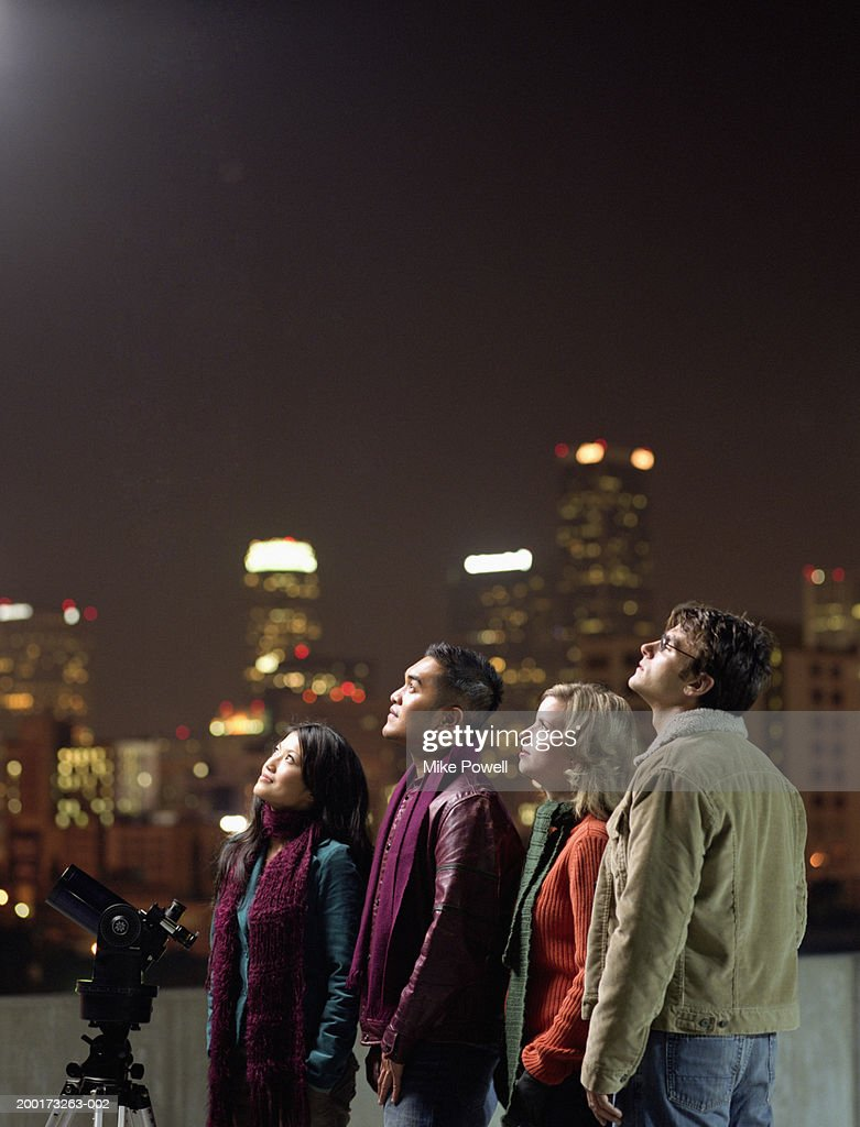 Two couples on rooftop, looking upwards at night sky : Stock Photo