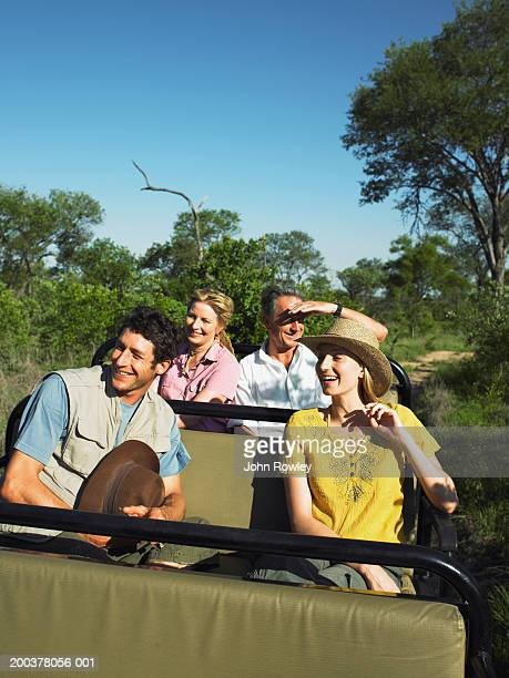 Two couples on safari being driven in 4x4, smiling