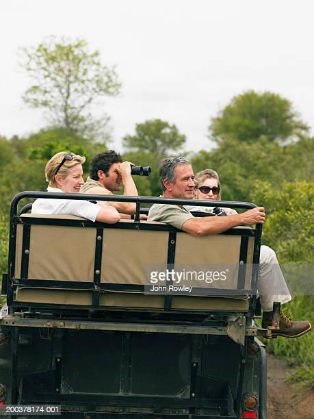 Deux couples sur safari en 4 x 4, homme à l'aide de jumelles