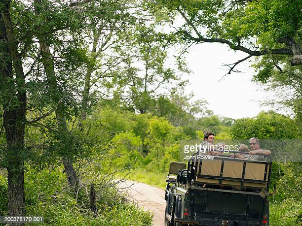 Two couples on safari sitting in 4x4 on track, smiling