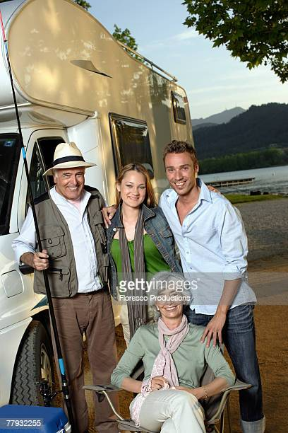 Two couples outside recreational vehicle with fishing pole