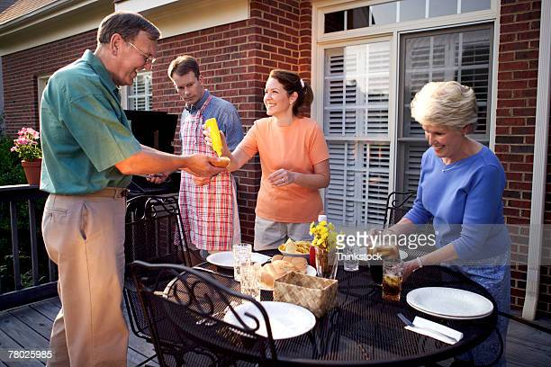 Two couples pass food and have fun while cooking out on the back porch