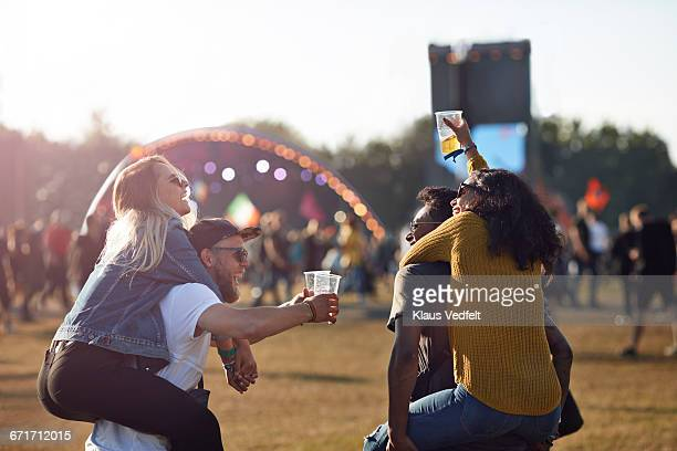two couples piggybacking at big festival outside - festival or friendship not school not business stock photos and pictures