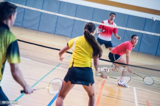 Two couples playing badminton