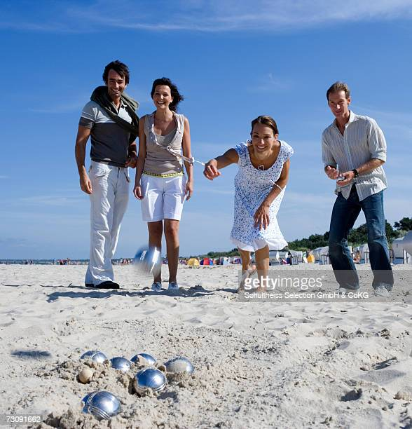 Two couples playing boules on beach