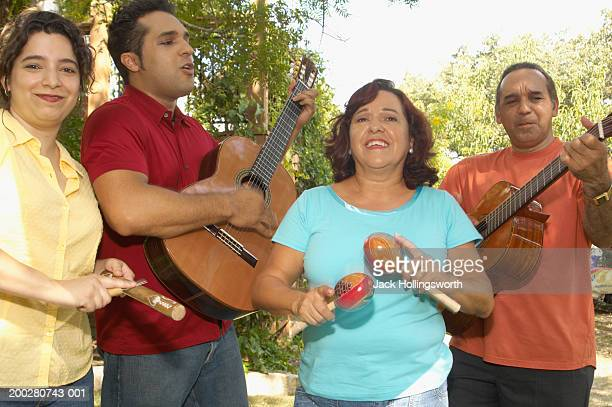 Two couples playing guitars and maracas