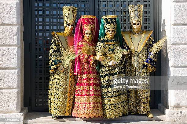 two couples posing in carnival costumes and masks during the venice carnival, punta della dogana, dorsoduro district. - プンタデラドガーナ ストックフォトと画像