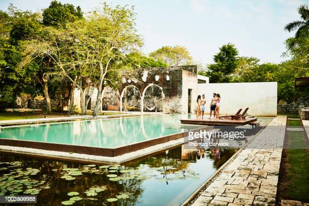 Two couples relaxing by edge of pool at luxury tropical resort