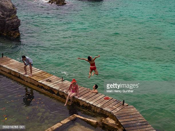 Two couples relaxing on dock, woman jumping into water, elevated view