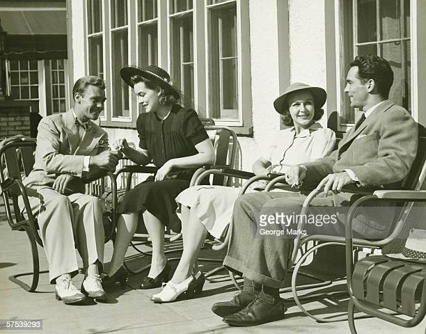 Two couples relaxing outside, (B&W)