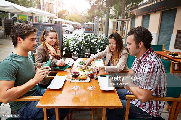 two couples sharing tapas at restaurant - tapas stock photos and pictures