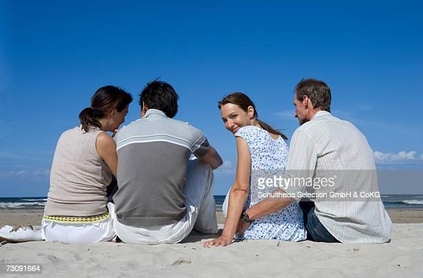 two couples sitting on beachrear view - 半そで ストックフォトと画像