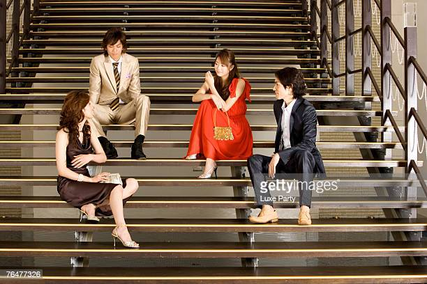 Two couples sitting on steps