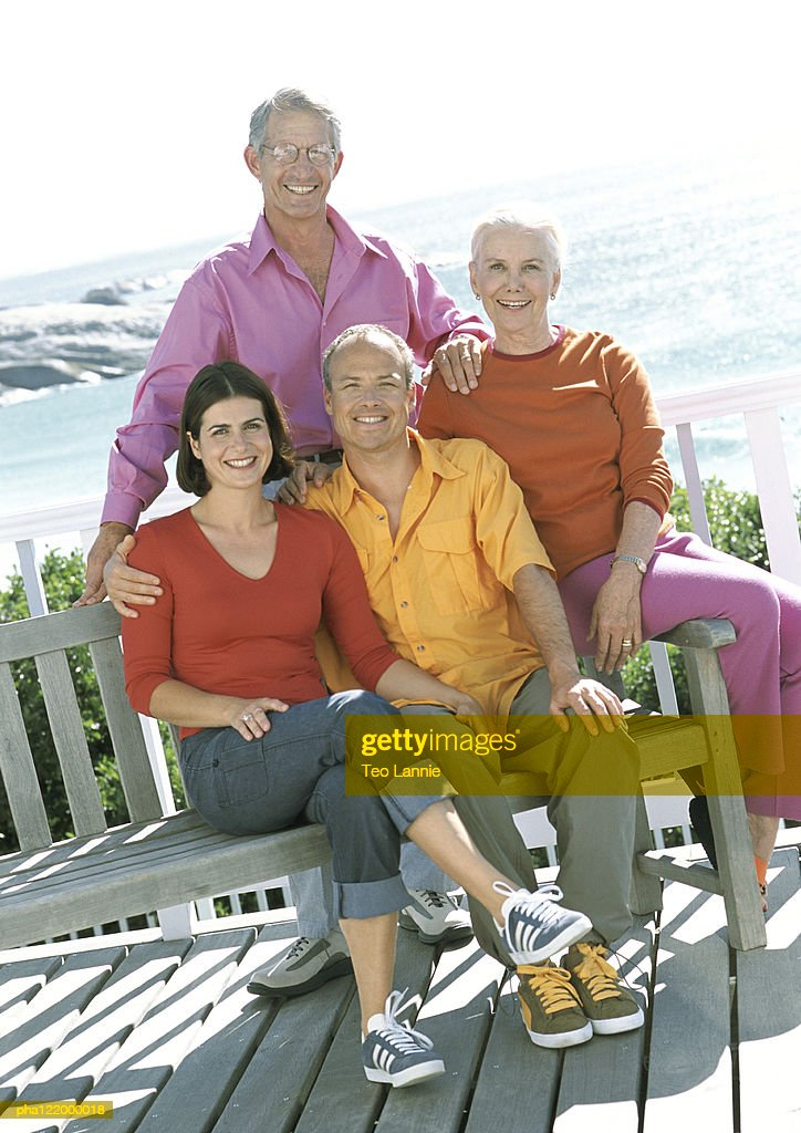 Two couples smiling, sea in background : Stockfoto