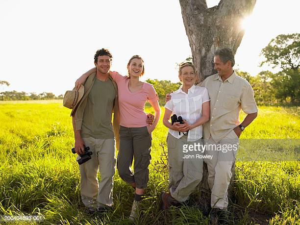Two couples standing arm in arm by tree, smiling (sun flare)