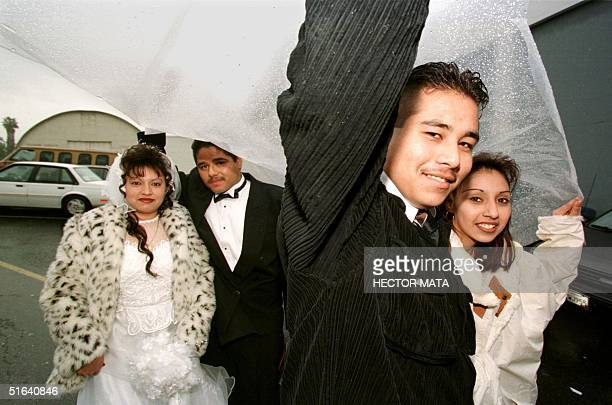 WITH EEUUAMOR BY CLAUDIA RAHOLA Two couples take cover against the rain as they queue outside the Hollywood Paladium for a wedding ceremony on Saint...