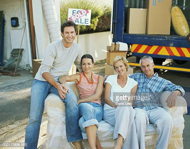 Two couples taking break on sofa by removal van, smiling, portrait