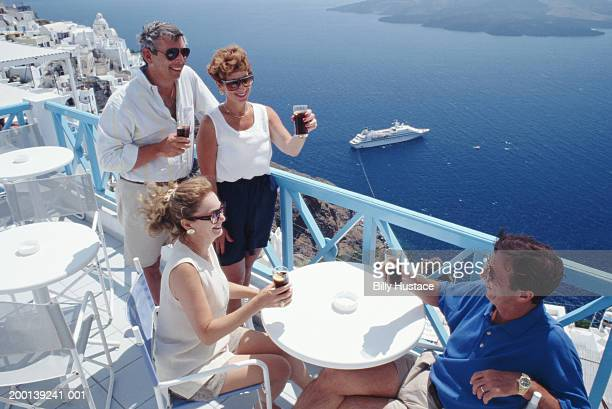 Two couples toasting drinks on balcony by ocean, elevated view