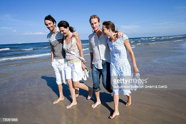 Two couples walking on beach