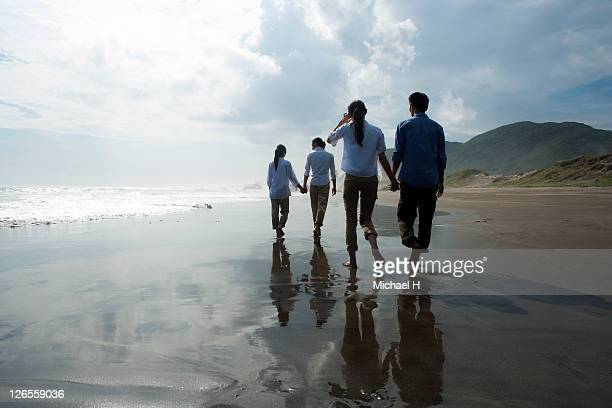 Two couples who walk along a beach